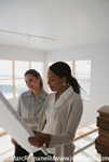 Stock Photos of a black woman with a pony tail going over blue prints of a construction project with another woman.